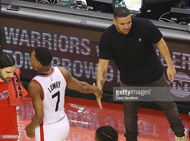 Drake shakes hands with Kyle Lowry of the Toronto Raptors during the game against the Cleveland Cavaliers in Game Four of the Eastern Conference...