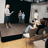 Drama Teacher Sits Directing Children as They Rehearse on Stage