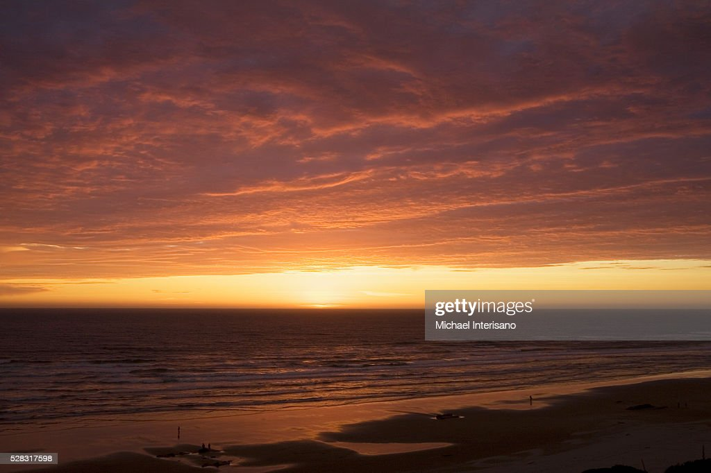 Dramatic Clouds At Sunset On A Beach With The Light Reflecting In The Ocean; Lincoln City Oregon United States Of America