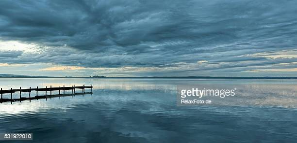 Dramatic cloudscape and jetty at dusk with reflection on lake
