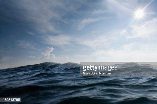 dramatic dark sea with sun in sky