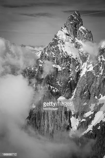 Dramatic monochrome mountain peak thrusting through swirling clouds