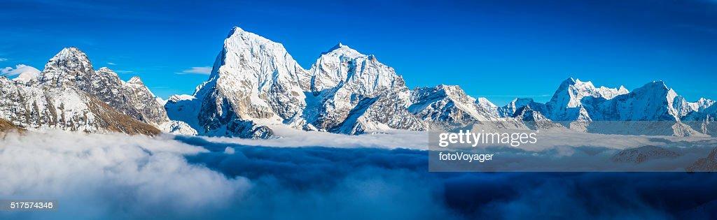 Dramatic mountain peaks panorama snowy summits above clouds Himalayas Nepal