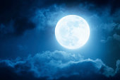 Dramatic photo illustration of a nighttime sky with brightly lit clouds and large, full, Blue Moon would make a great background.