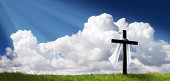This dramatic Easter Morning Sunrise panorama with blue sky, sunbeams, and large cross on a grass covered hill makes a great banner cover for print or web.