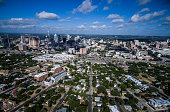 Dramatic Perspective Over East Austin Texas Aerial Cityscape over East side looking west with the Texas Hill Country background behind the Skyline of the Capital City on a spotted clouded Blue Sky mor