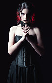 Dramatic portrait of a beautiful goth woman among the dark