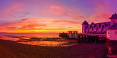 Dramatic sky in yellow, red and magenta colors and Penarth Pier before sunrise. Panorama image.