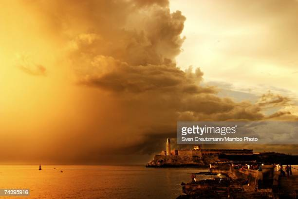 A dramatic sky looms over Castillo El Morro lighthouse as people stroll the coastal oceanfront Malecon highway at sunset on July 25 2004 in Havana...