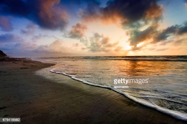 Dramatic sky reflection on a tropical beach at sunrise
