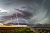 A powerful supercell thunderstorm with a pair of dramatic forked lightning strikes, spins across Texas.