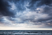 Dramatic stormy dark cloudy sky over sea, natural photo background