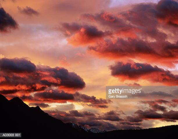 Dramatic sunrise over rocky peaks, dark cumulus clouds tinged with red