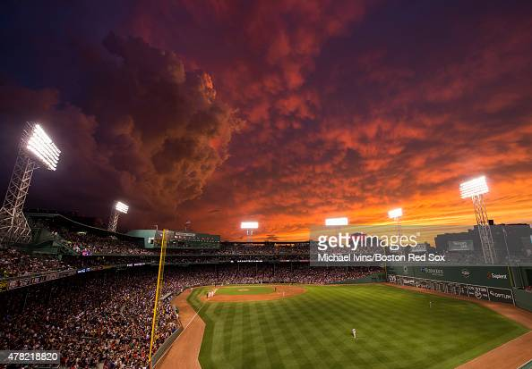 A dramatic sunset illumines the sky during a game between the Boston Red Sox and the Baltimore Orioles at Fenway Park in Boston Massachusetts on June...