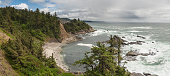 White surf crashing onto the dramatic rocky coastline of Oregon, with pine forest bluffs overlooking the beaches and blue Pacific Ocean at Cape Arago, USA. ProPhoto RGB profile for maximum color fidel
