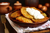 Draniki - potato pancakes stuffed with minced meat,traditional dish of east slavic cuisine on a ruatic background.