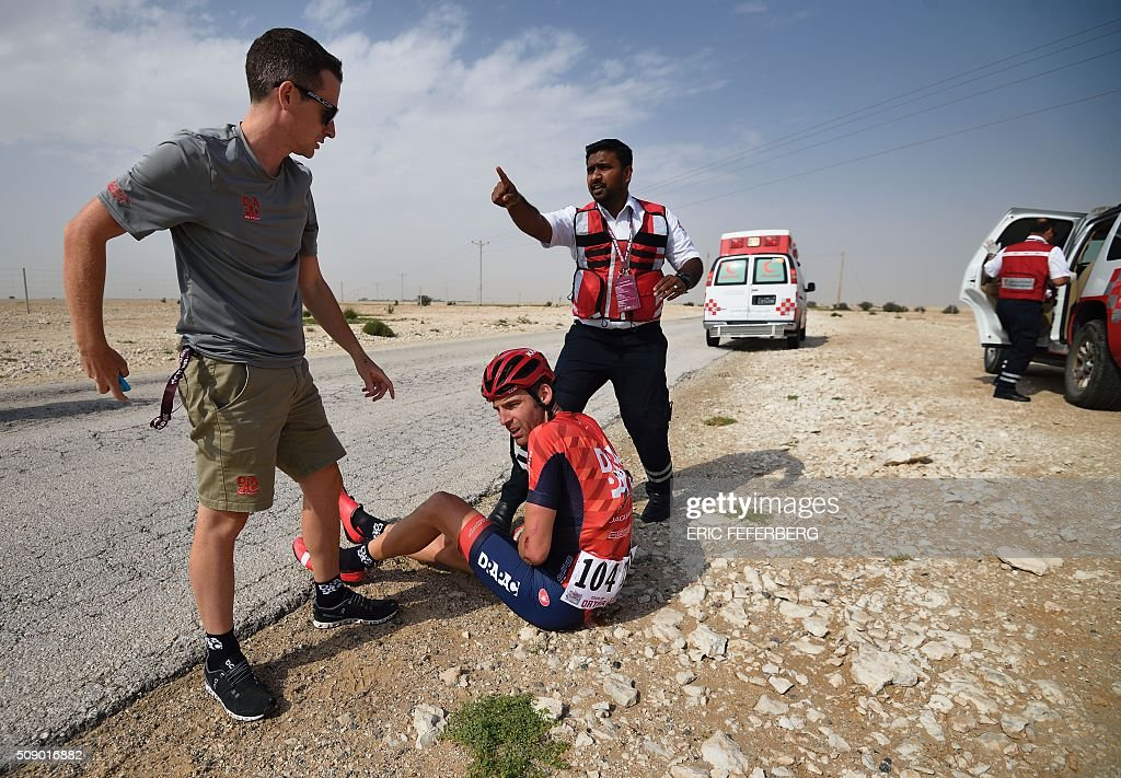 Drapac team's Dutch Peter Konning is assisted after falling during the first stage of the 2016 Tour of Qatar, between Dukhan and Al Khor Corniche on February 8, 2016. Britain's Mark Cavendish, the former world road race champion, took the gold jersey and covered the 175 kilometres from Dukhan to the Al Khor corniche, north of the capital Doha, in 3hrs 28.31secs, eight seconds in front of Modolo and 11 seconds ahead of Guardini. / AFP / ERIC FEFERBERG