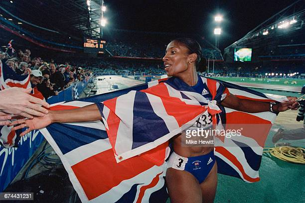 Draped in the Union flag Denise Lewis of Great Britain celebrates winning the gold medal for the Women's Heptathlon event during the XXVII Olympic...