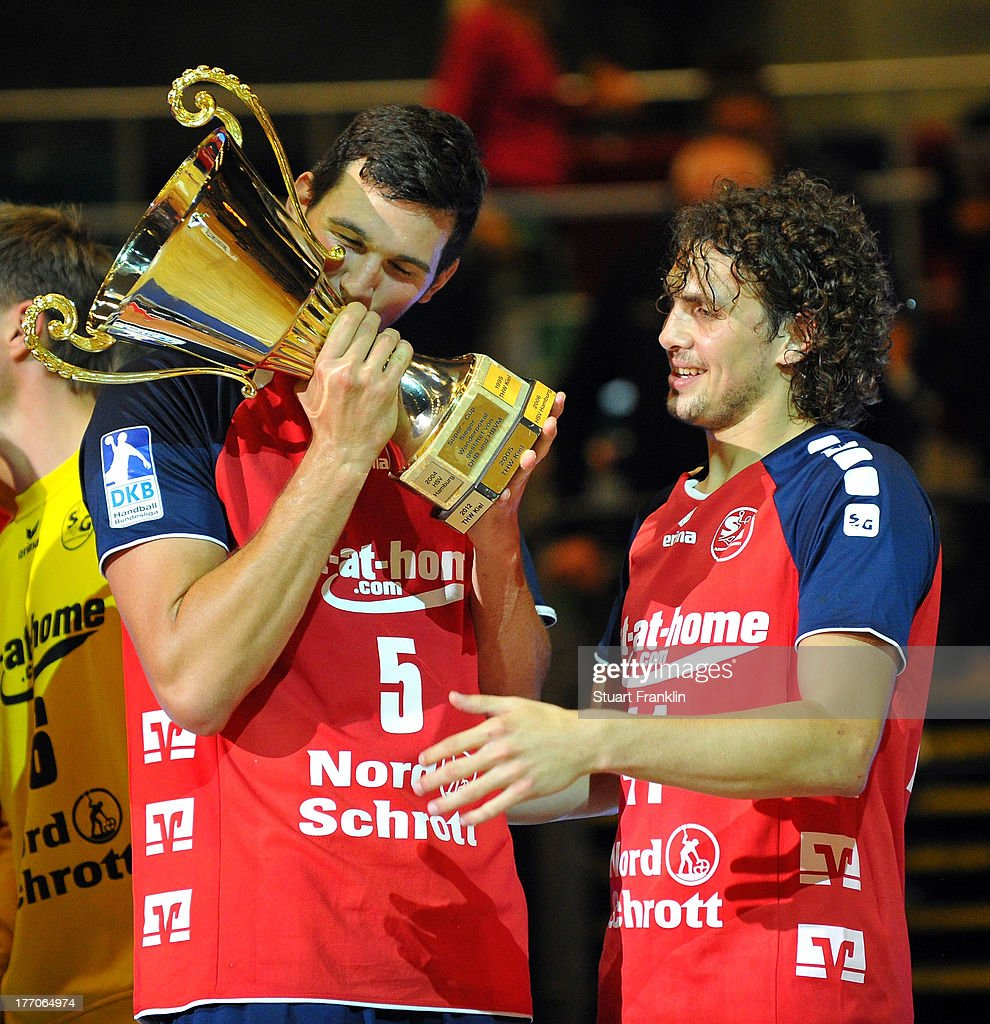 Drasko Nenadic and Bogdan Radivjevic of Flensburg with the trophy after the DKB supercup match between THW Kiel and Flensburg Handewitt at the OVB arena on August 20, 2013 in Bremen, Germany.