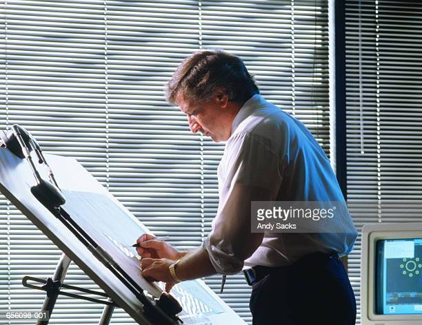 Draughtsman standing,working at drawing-board,terminal behind