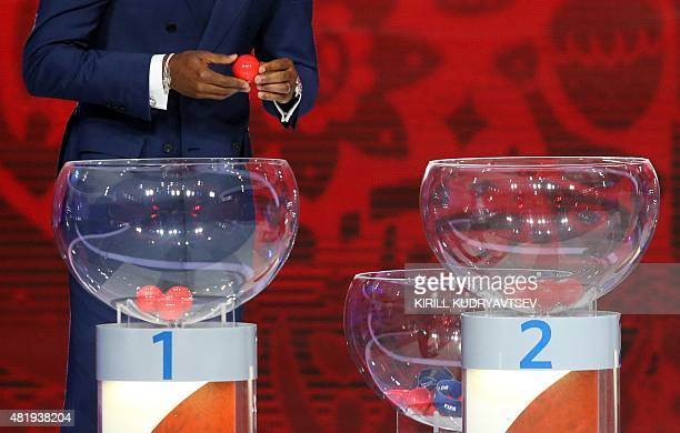 A draw assistant waits to reveal the name of a country during the preliminary draw for the 2018 World Cup qualifiers at the Konstantin Palace in...