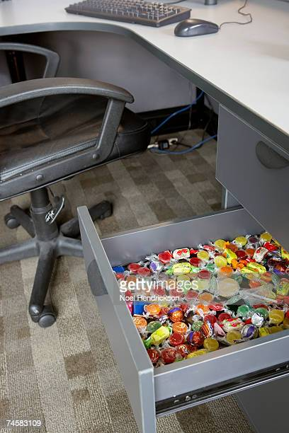 Drawer full of candy in office desk, elevated view