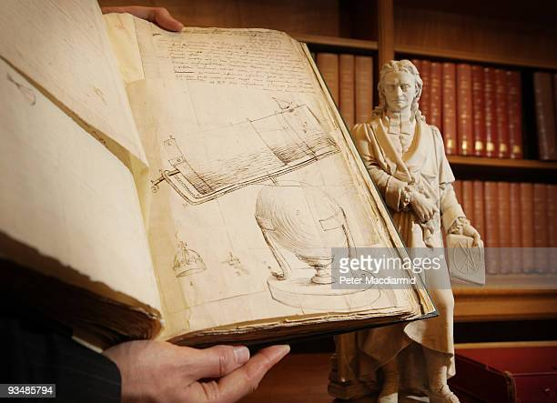 A drawing by Isaac Newton of his telescope contained in a book of his letters is displayed next to a statue of him at the Royal Society on November...