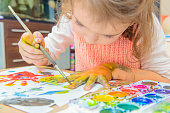 girl drawing paints on paper and hands