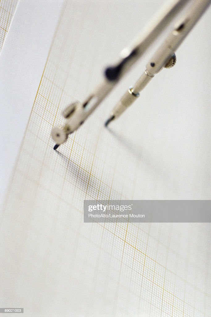 Drawing compass on graph paper : Stock Photo