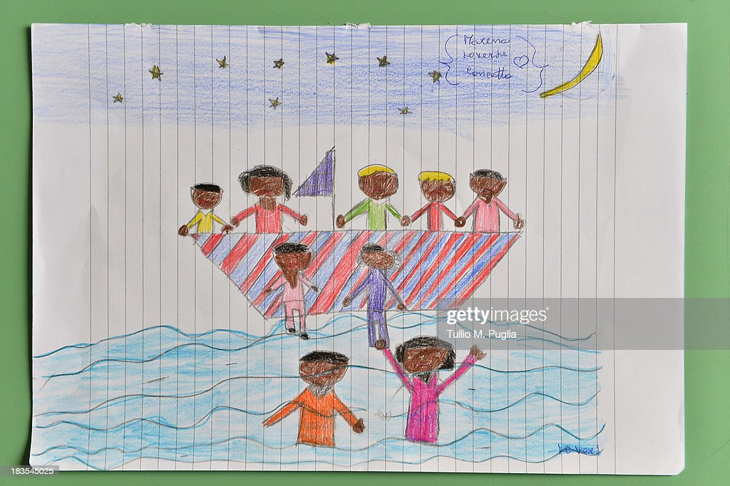 A drawing created by a student relating to the recent shipwreck off the Italian coast are displayed in the Elementary School of Lampedusa on October 7, 2013 in Lampedusa, Italy. The search for bodies continues off the coast of Southern Italy as the death toll of African migrants who drowned as they tried to reach the island of Lampedusa is expected to reach over 300 people. The tragedy has bought fresh questions over the thousands of asylum seekers that arrive into Europe by boat each year.