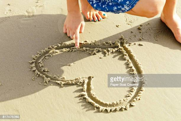 drawing heart in the sand on a beach on a sunny day