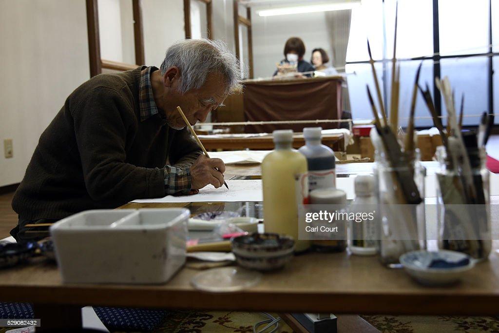 Drawing master Kenji Suhara draws the outline of designs on kimono fabric during a stage of its production process at the Sensyo Ichikawa kimono...
