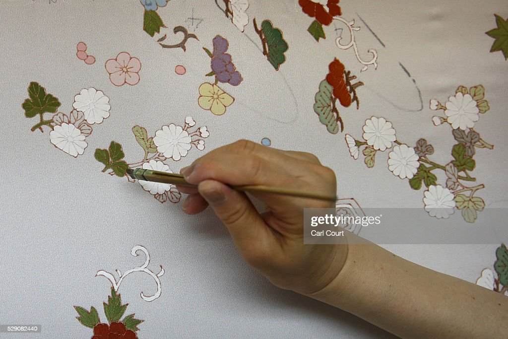 Drawing master Takako Yoshida paints a design on kimono fabric during a stage of its production process at the Sensyo Ichikawa kimono workshop on...