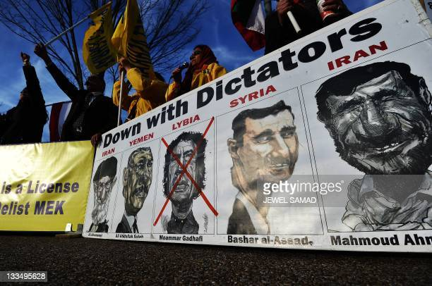 A drawing of former Libyan dictator Moamer Kadhafi is marked with red cross on a poster displayed by relatives of residents of Camp Ashraf in Iraq...