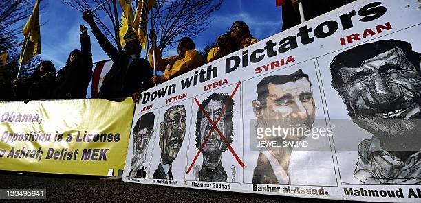 A drawing of former Libyan dictator Moamer Kadhafi is marked with red cross in a poster displayed by relatives of residents of Camp Ashraf in Iraq...