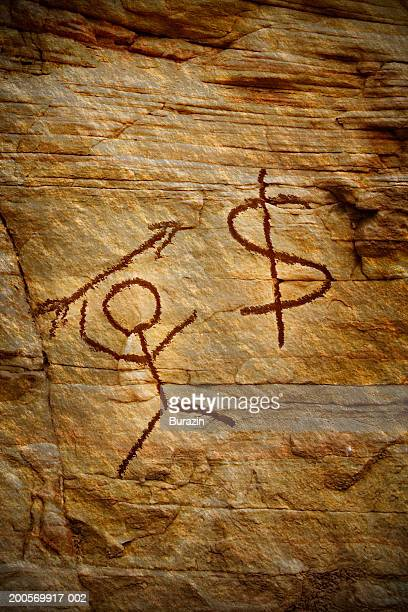 Drawing of stick man and dollar sign on cave wall