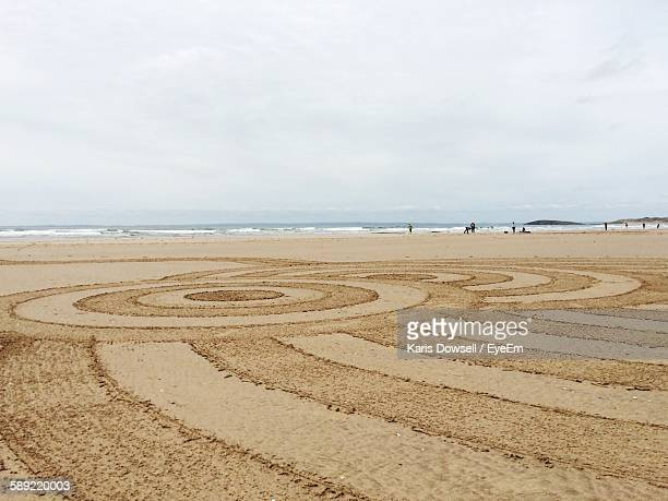Drawing On Sand At Beach Against Sky