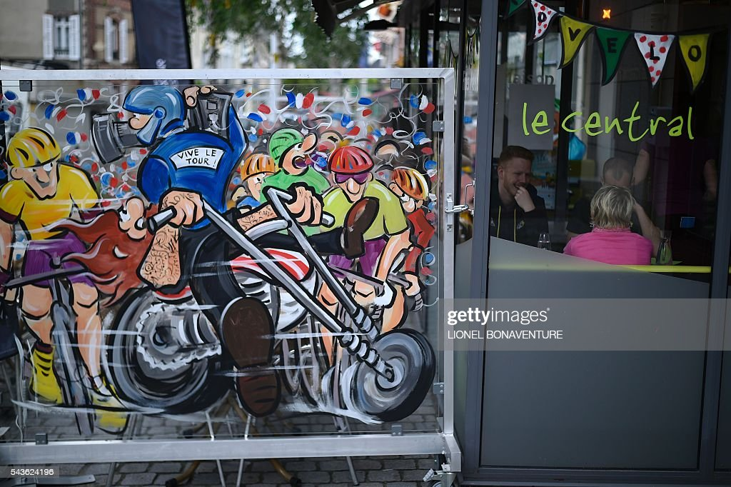A drawing representing a cameraman and cyclists, reads 'Long life the Tour de France !', on the window of a cafe in Saint-Lo, Normandy, on June 29, 2016, three days before the start of the 103rd edition of the Tour de France cycling race. The 2016 Tour de France will start on July 2 in the streets of Le Mont-Saint-Michel and ends on July 24, 2016 down the Champs-Elysees in Paris. / AFP / LIONEL