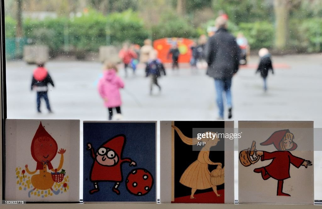 Drawings for children are on display in a classroom while pupils run in the playground of a school in Lille, nothern France, on March 18, 2013.