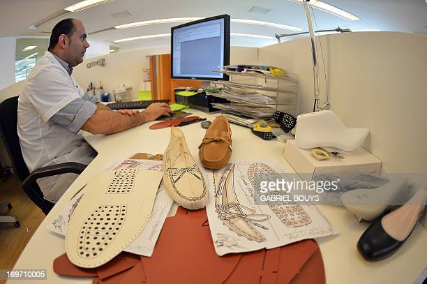 Drawings of mocasins prototypes are displayed on the desk of a technician of the Italian shoes and luxury leather goods Tod's on May 27 2013 in...