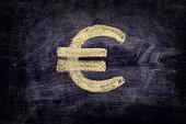 Drawn euro sign on black chalkboard background. Close up.