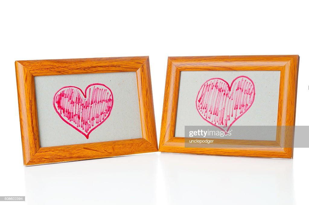 Drawn hearts in the photo frames : Stock Photo
