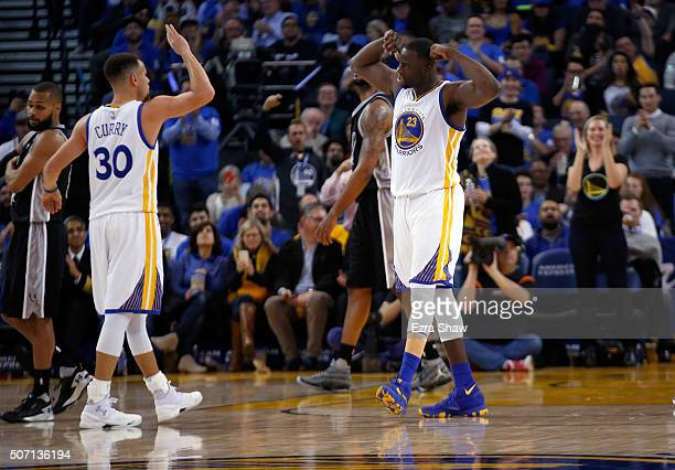 Draymond Green and Stephen Curry of the Golden State Warriors react after the Warriors made a basket against the San Antonio Spurs at ORACLE Arena on...