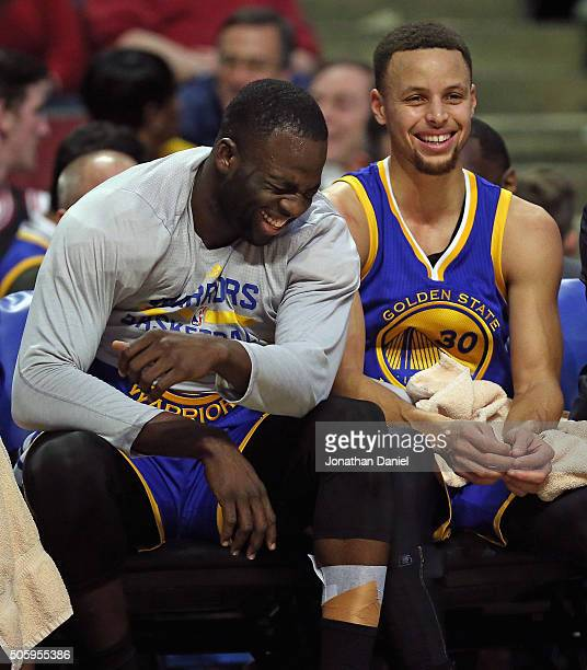 Draymond Green and Stephen Curry of the Golden State Warriors share a laugh on the bench near the end of a game against the Chicago Bulls at the...