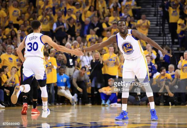 Draymond Green high fives Stephen Curry of the Golden State Warriors after the Warriors made a basket against the Portland Trail Blazers in Game Two...