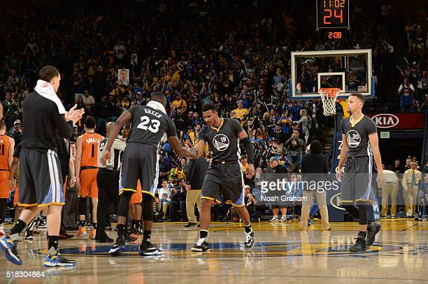 Draymond Green high fives teammate Leandro Barbosa of the Golden State Warriors during the game against the Phoenix Suns on March 12 2016 at Oracle...