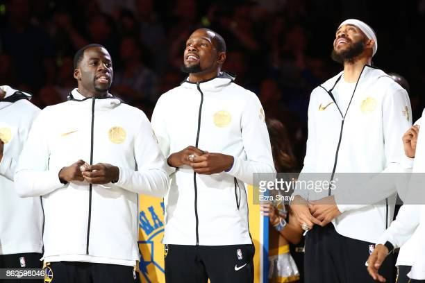 Draymond Green Kevin Durant and JaVale McGee of the Golden State Warriors stand during their 2017 NBA Championship ring ceremony prior to their NBA...