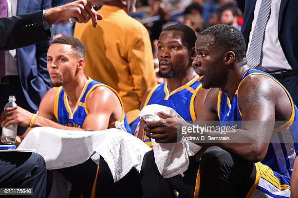 Draymond Green Kevin Durant and Stephen Curry of the Golden State Warriors look on during a game against the New Orleans Pelicans at Smoothie King...