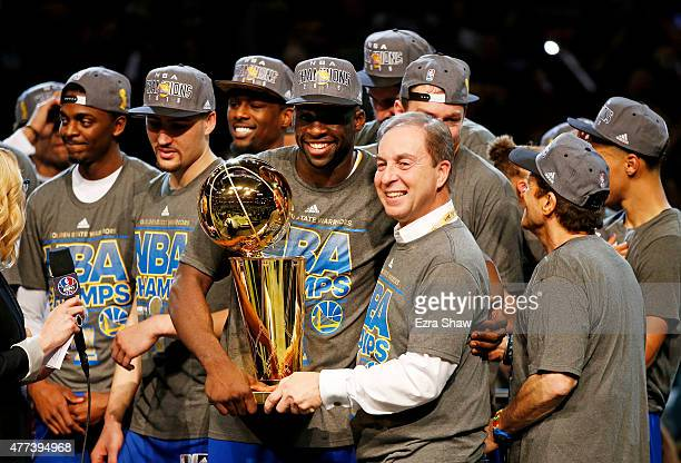 Draymond Green of the Golden State Warriors celebrates with team owner Joe Lacob and the Larry O'Brien NBA Championship Trophy after defeating the...