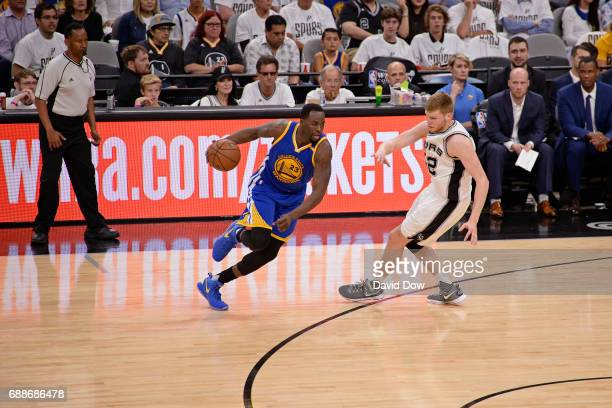 Draymond Green of the Golden State Warriors dribbles the ball around Davis Bertans of the San Antonio Spurs in Game Four of the Western Conference...